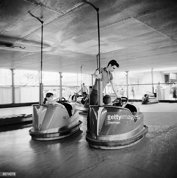 An employee of Palisades Amusement Park New Jersey adjusts the steering wheel of one of the dodgem cars from a rather dangerous position
