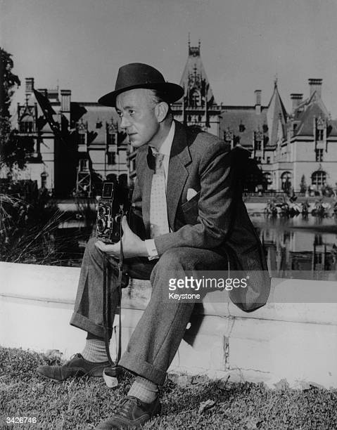 British actor Alec Guinness spends some spare time taking photographs during his first visit to Hollywood