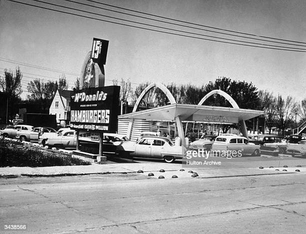 Exterior of a McDonald's drivein fast food restaurant which advertises 15cent hamburgers