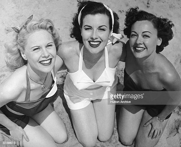 High angle view of three women wearing swimsuits kneeling arminarm on a sandy beach smiling at the camera