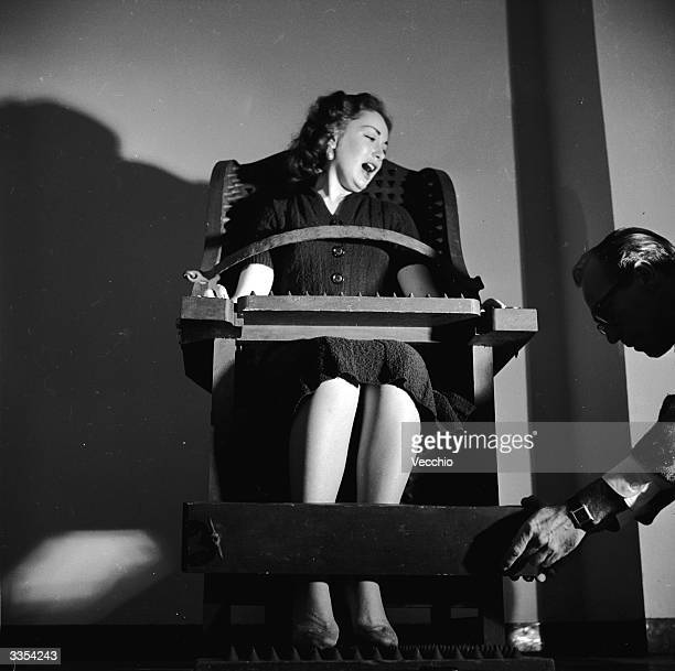 Jacob Macken of Ripley's Odditorium in New York city prepares to torture actress Francine Barrera in a torture chair designed to apply spikes as the...