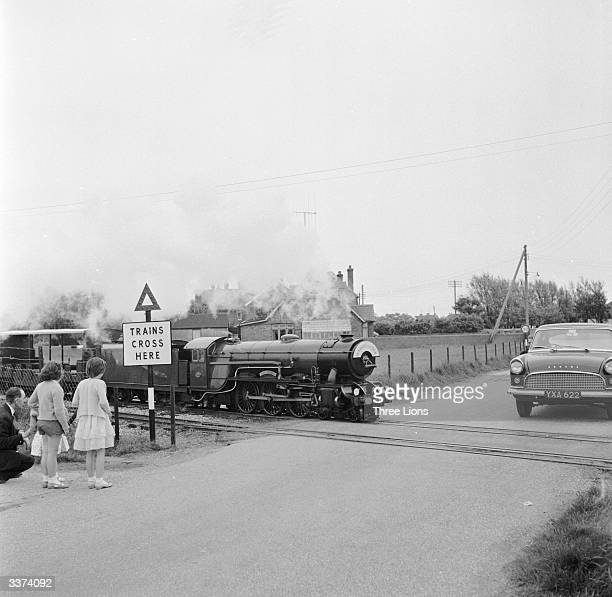 One of the engines of the Romney, Hythe and Dymchurch Light Railway passes a level crossing in front of a car not much smaller than itself. The line...