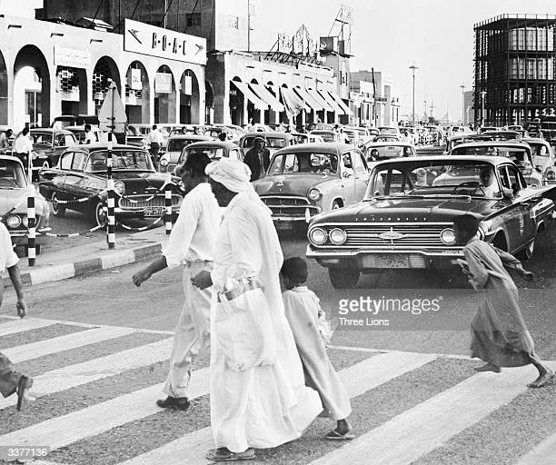 People crossing a busy street in central Kuwait City