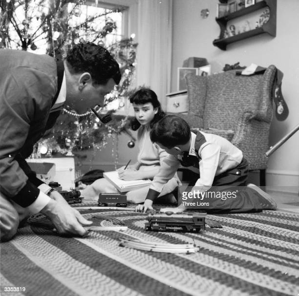 Radio and television announcer Frank Blair helps his son with a brand new model train set on Christmas morning