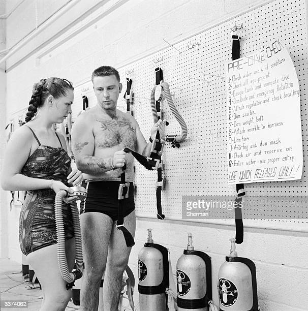 Scuba diving teacher Roger Himes explains the mechanisms of an aqualung to his student at the Central Scubatorium. A sign in front of them lists the...
