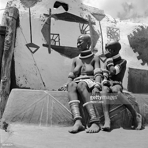Two girls of the Ndebele tribe wearing brass bracelets around their ankles and sitting on a decorated wall in their village
