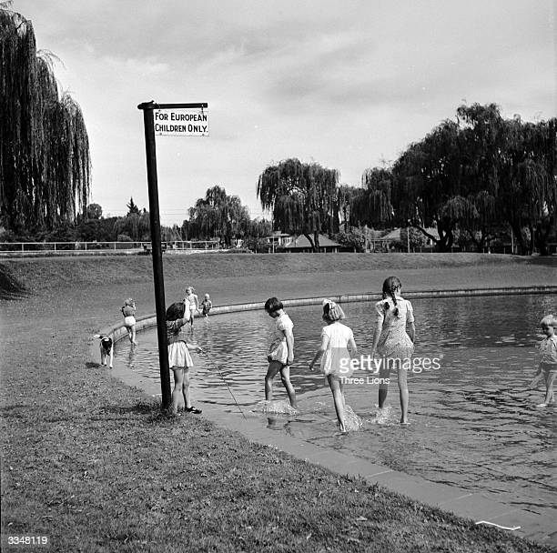 White children paddling in a pond marked by a sign reading 'For European Children Only'
