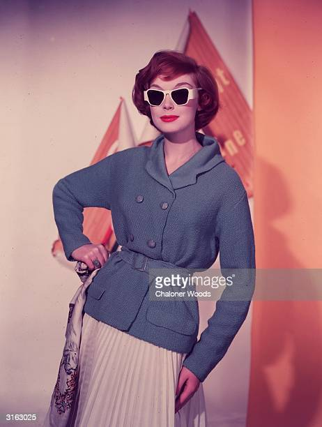 A fifties fashion model wearing a pleated skirt and a hiplength doublebreasted cardigan with side pockets