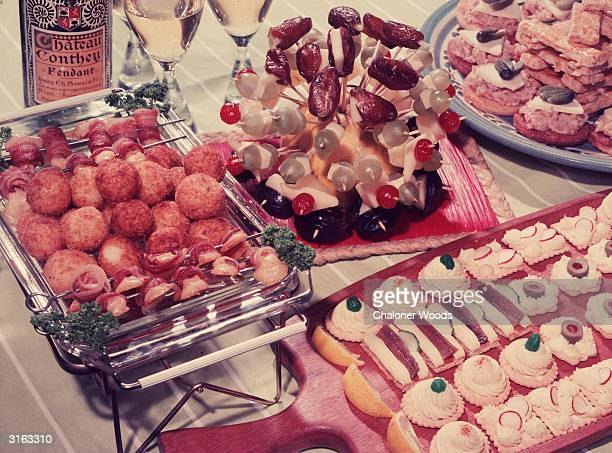 A fruit salad buffet arrangement on cocktail sticks accompanies barbecued meat on skewers croquette potatoes savouries on crackers and canapes served...