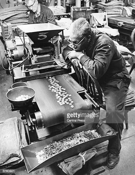 A worker checks coins along a conveyor belt at the Royal Mint