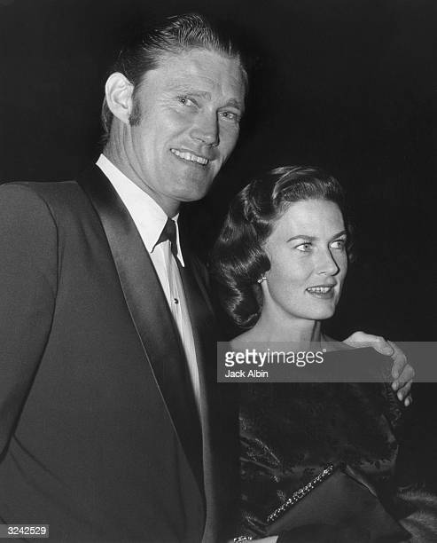 American actor and former baseball player Chuck Connors smiles as he stands with his arm around his wife Elizabeth Jane Riddell at an ABC party at...