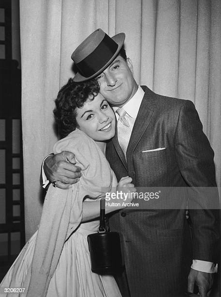 American actor Danny Thomas embraces American actor and singer Annette Funicello in front of a stage curtain late 1950s Thomas wears a jacket and a...