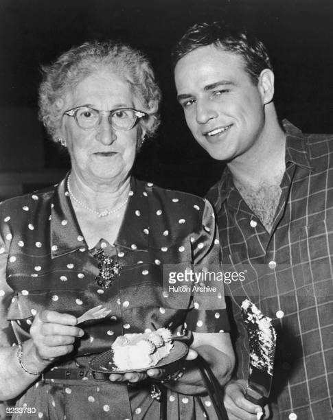 American actor Marlon Brando smiles beside his aunt Mrs June Beachly after cutting his birthday cake on the set of director Joshua Logan's film...