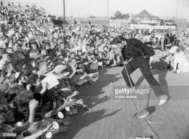 American singer and actor Elvis Presley performing outdoors on a small stage to the adulation of a young crowd.