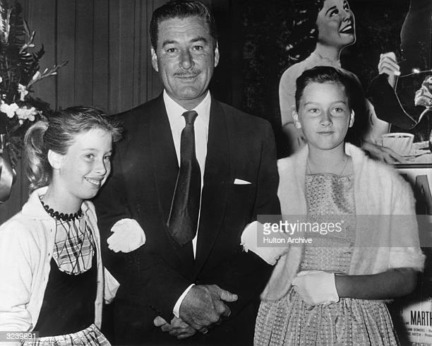 Australianborn actor Errol Flynn poses with his daughters Rory and Deirdre on his arms as they attend a formal event