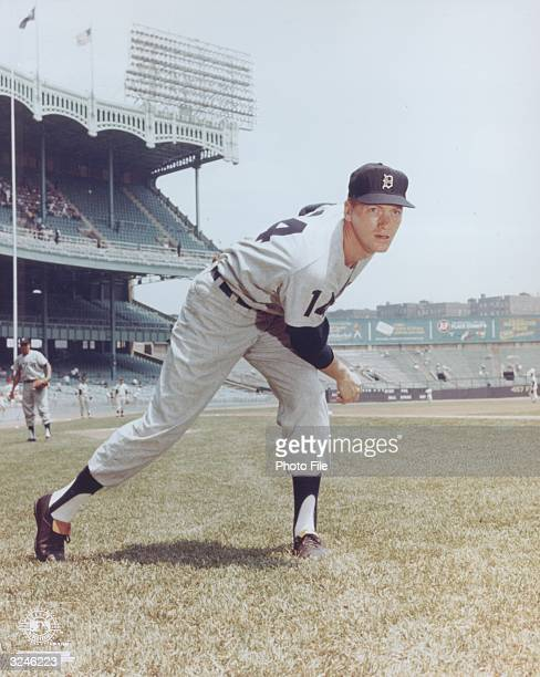 Detroit Tigers pitcher Jim Bunning pitches during a practice game bending forward with one leg stretched back late 1950s