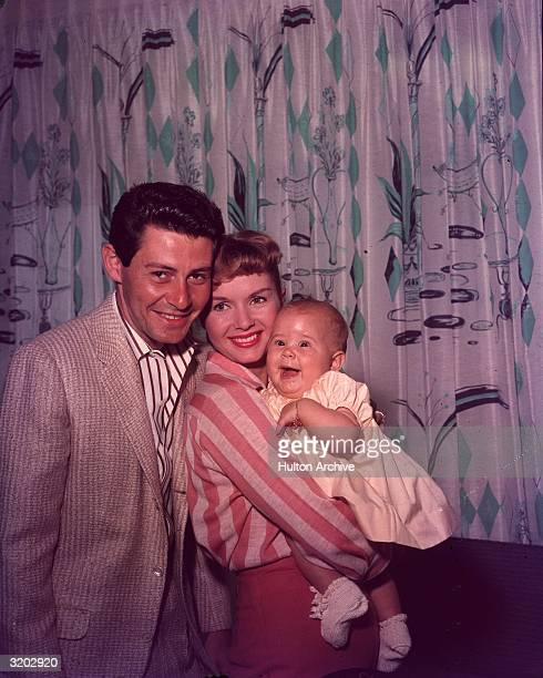 Family studio portrait of married American singer/actors Eddie Fisher and Debbie Reynolds with their daughter Carrie Fisher