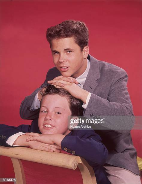 Promotional portrait of American actor Tony Dow as Wally leaning on American actor Jerry Mathers as his brother Beaver for the television series...