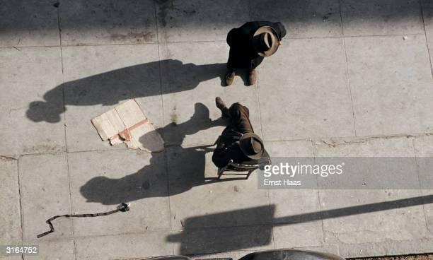 Sitting on the pavement a 3rd Avenue 'clothes dealer' talks to a prospective customer