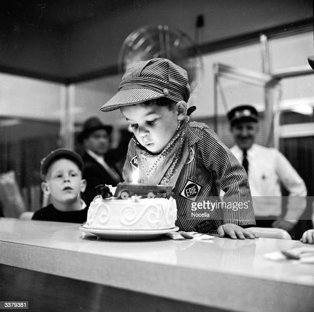 A young boy prepares to blow out the candles on a birthday cake