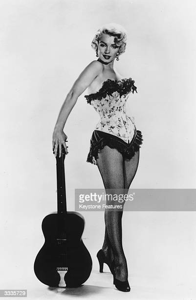 Actress and archetypal sex symbol Marilyn Monroe corsetted and wielding a guitar