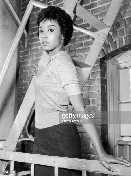 American actor and singer Diahann Carroll standing on a fire escape balcony in a promotional portrait for her appearance on the 'Sing a Song of...