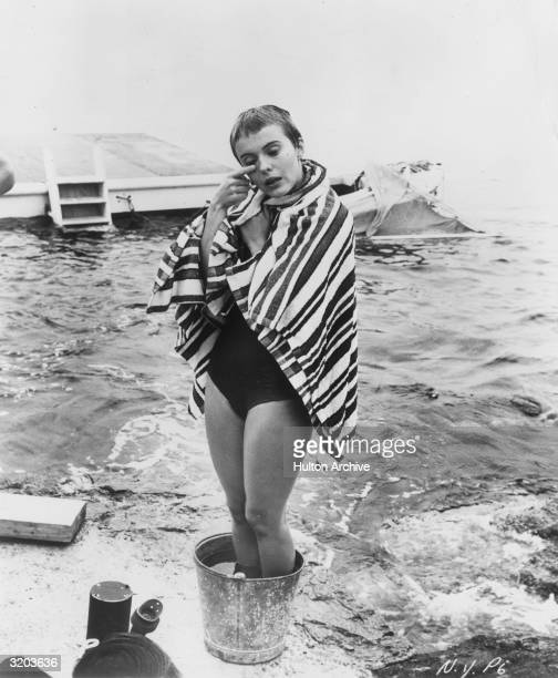 American actor Jean Seberg wears a bathing suit on the beach standing with her feet in a bucket of water on the set of director Otto Preminger's film...