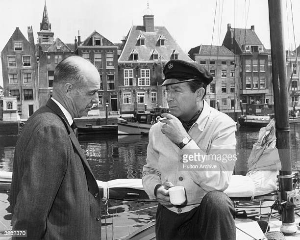 American actor Robert Taylor in a sailor's cap holds a cigarette and a coffee mug as he talks to American film director Richard Thorpe on the set of...