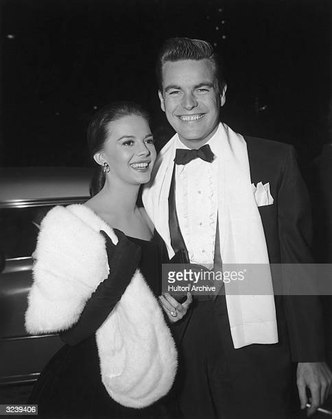 American actors Natalie Wood wearing a black evening gown with long gloves and a white fur wrap and Robert Wagner wearing a tuxedo with a white opera...
