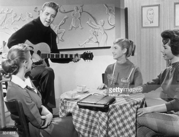 American rockabilly singer Eddie Cochran plays the guitar and sings to three young women in a still from director Paul Landres' film 'Go Johnny Go'