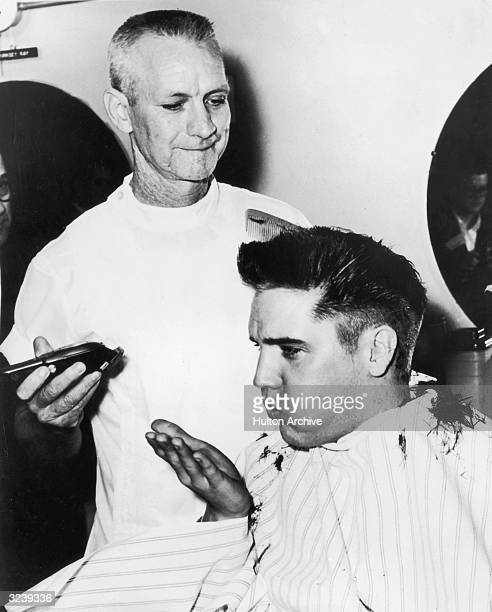 American singer and actor Elvis Presley blows a strand of hair from his hand, while receiving a haircut from a US Army barber, Fort Chaffee,...