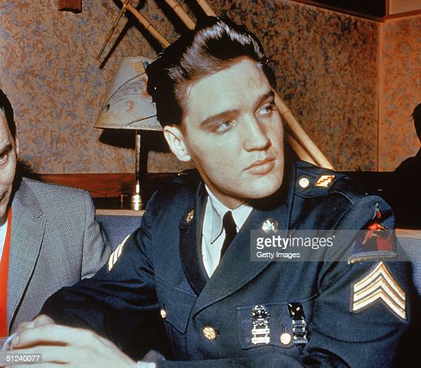Circa 1958 American singer and actor Elvis Presley sits in a restaurant wearing his US Army uniform