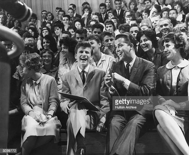 American singer and musician Bobby Rydell sits next to American television host Dick Clark in the audience of the television show, 'American...
