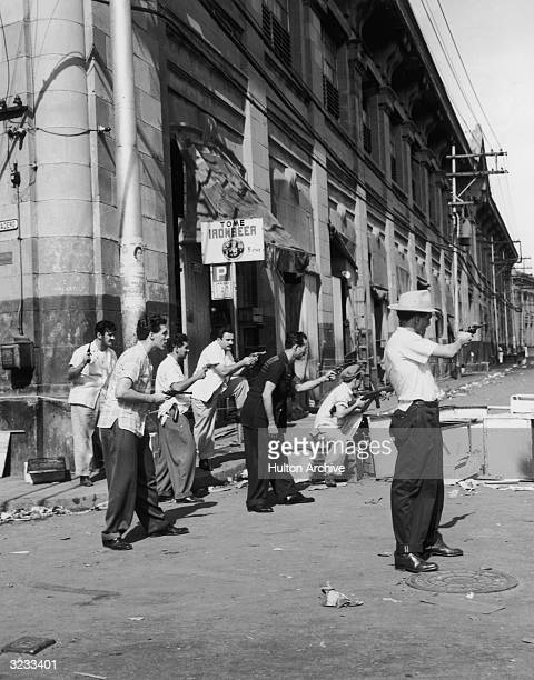 Armed Cuban Revolutionaries guard the entrance to one of Havana's central markets while enforcing the general strike that virtually paralyzed all of...