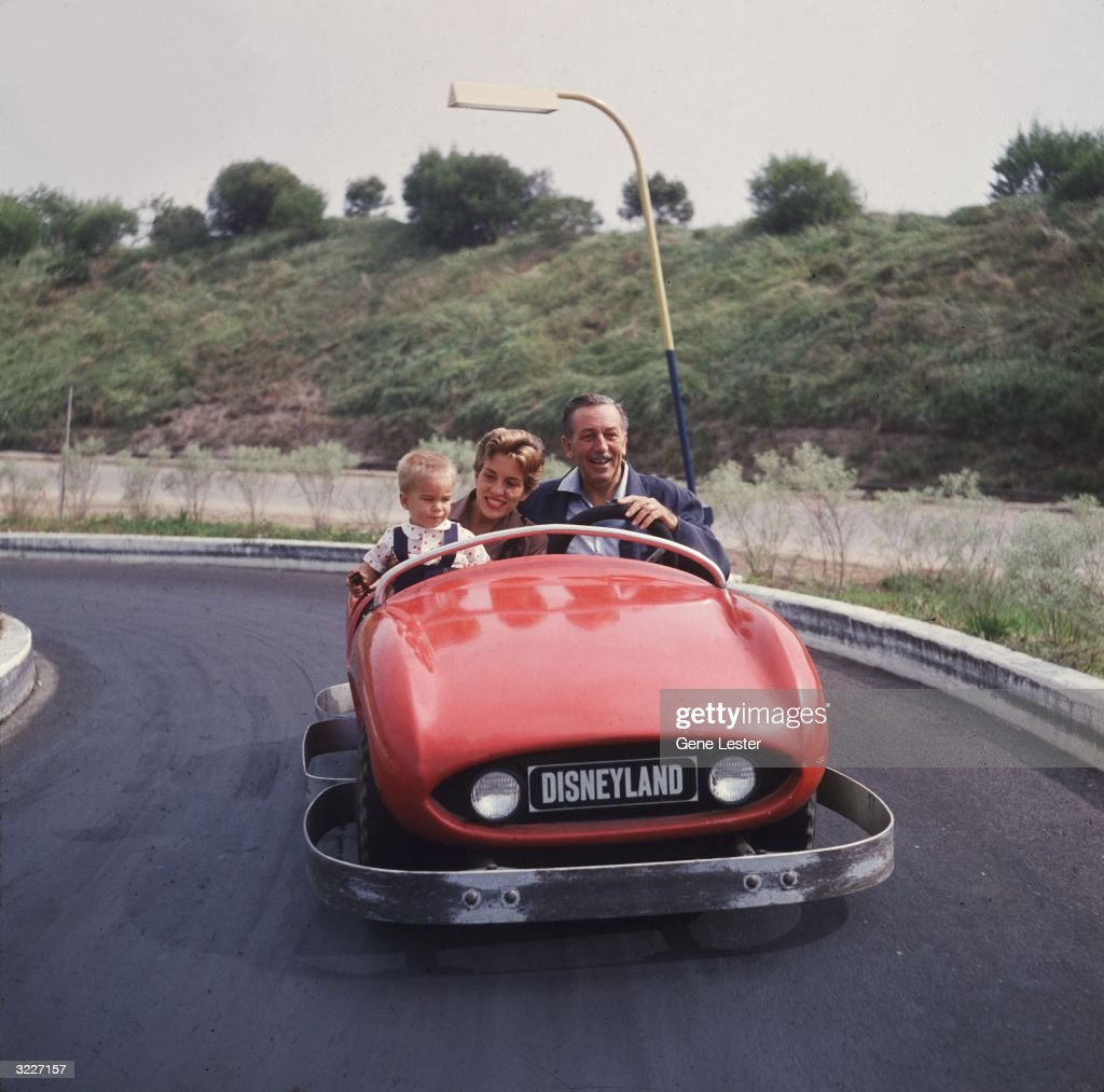 Walt Disney (1901 - 1966) drives a red bumper car with his daughter and grandson as passengers at Disneyland theme park, Anaheim, California.