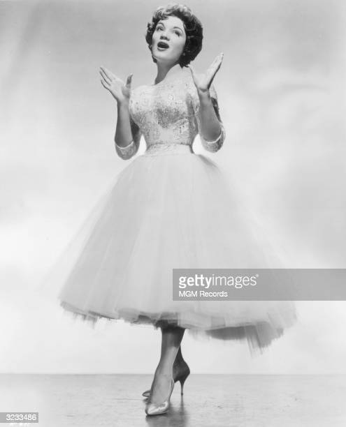 Fulllength portrait of American singer Connie Francis wearing a dress with a tulle skirt performing