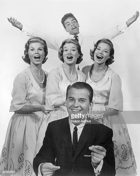 Group promotional portrait of American television personality Dick Clark snapping his fingers to the beat of a song as the McGuire Sisters, made up...