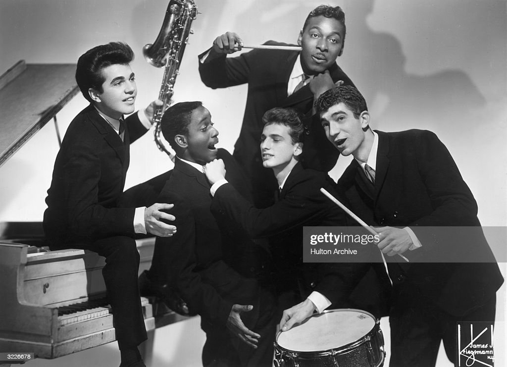 Promotional portrait of American rock 'n roll group Joey Dee and the Starliters clowning around. The saxophonist sits on a piano, and the drummer holds a drumstick to his cheek.