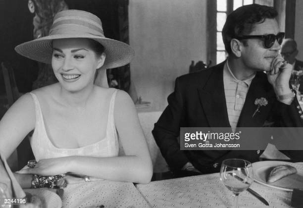 Swedishborn actor Anita Ekberg smiles as she sits outdoors at a table with her husband British actor Anthony Steel Ekberg wears a straw sun hat Steel...