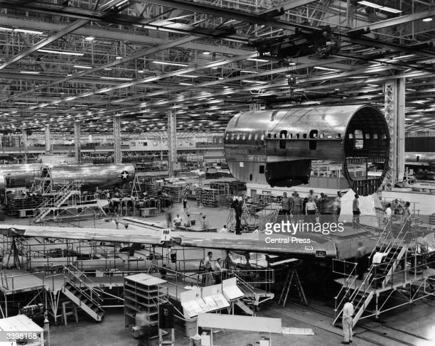 The centre fuselage section of Pan American Airlines first Boeing 707 Stratoliner jet being moved across the hangar to receive detail finishing