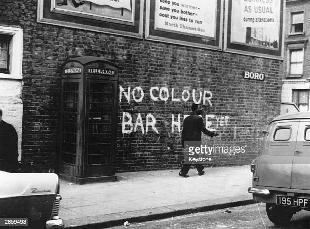 A black man walking down a Notting Hill Street where race riots had recently taken place The graffiti behind him reads 'No Colour Bar Here Yet'