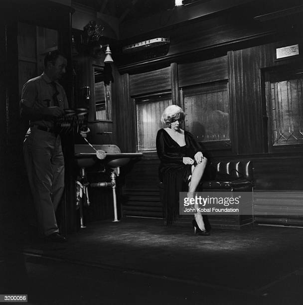 Actress Marilyn Monroe adjusts the top of her stocking as a man with a clapperboard signals a new take for 'Some Like It Hot' directed by Billy Wilder