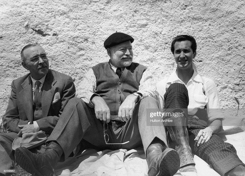 American author Ernest Hemingway (1899 - 1961), (centre) and Spanish bullfighter Luis Dominguin (right), smoking a cigarette, sit against a wall, Spain.