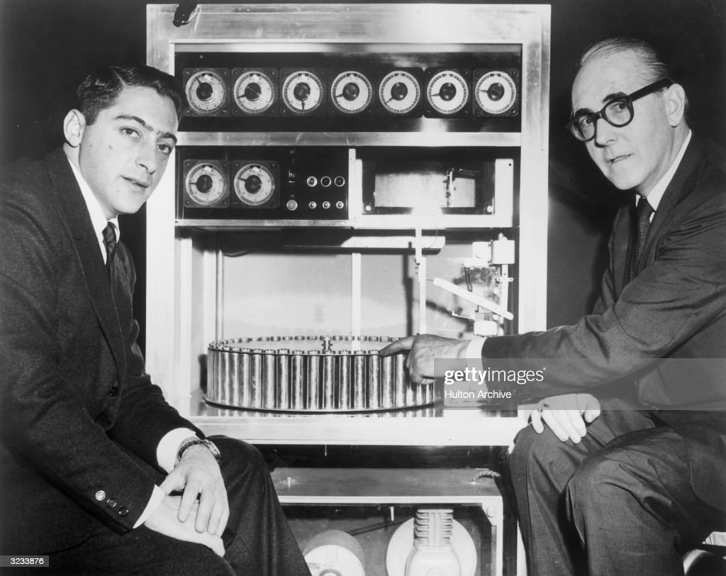 American film producer Mike Todd Jr (left) sits with Swiss inventor Hans Laube, who points to his 'Smell-O-Vision' machine, which produced smells in synchronization with action in a film. The device was used for director Jack Cardiff's 1960 film, 'The Scent of Mystery,' produced by Todd.