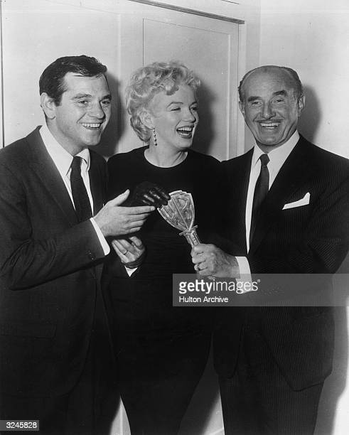 Left to right fashion photographer Milton H Greene American actor Marilyn Monroe and film producer Jack L Warner announce their agreement to do a...