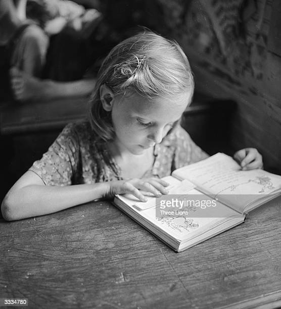 Child learns to read in a one room, rural grade school in Leslie County, Kentucky, USA.