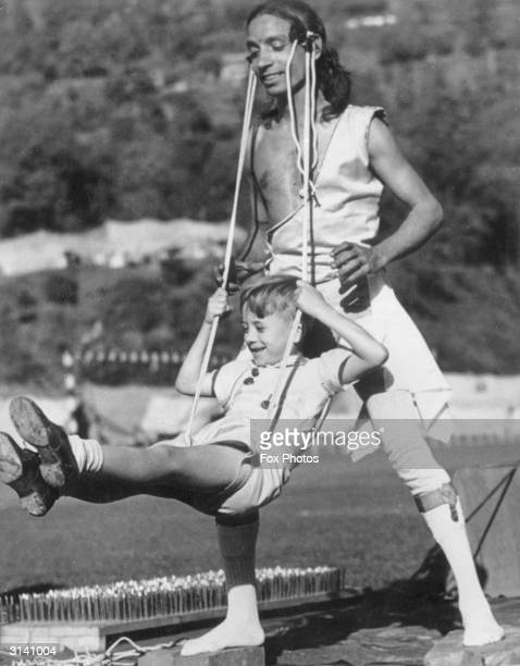A child swings suspended in a sling attached to the hair of a yogi practitioner they both appear to be enjoying the experience The occasion is a yoga...