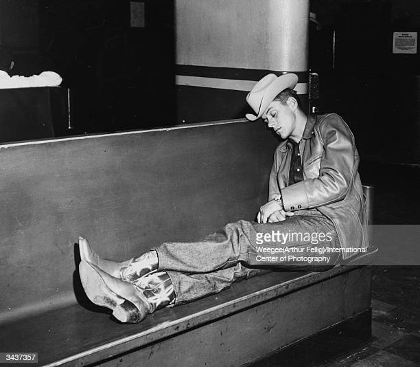 A cowboy asleep on a bench in a bus station in Denver Colorado Photo by Weegee/International Center of Photography/Getty Images