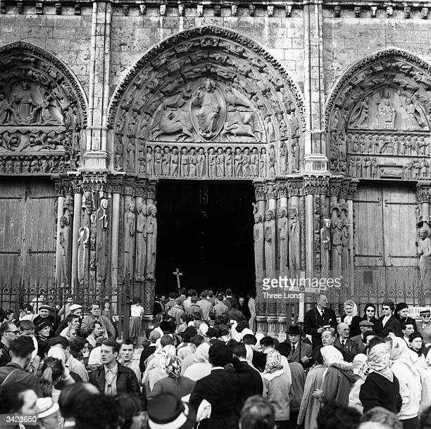 A crowd of people entering Chartres Cathedral following their pilgrimage to the medieval French town