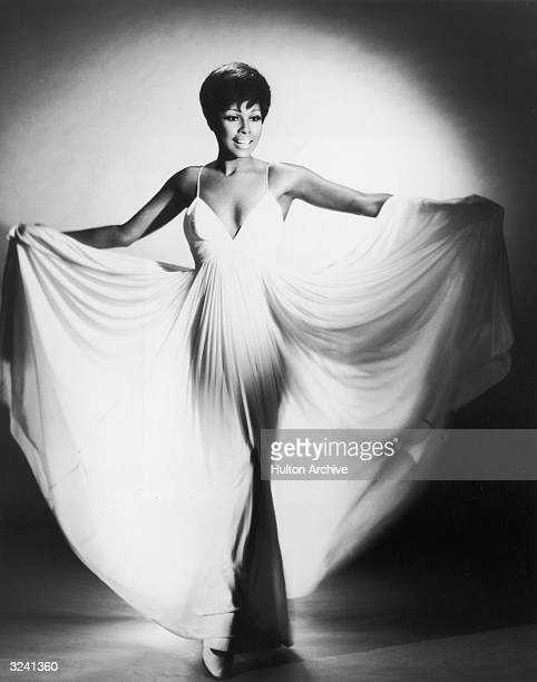 A fulllength studio portrait of American actor Diahann Carroll fanning her long white dress with her arms